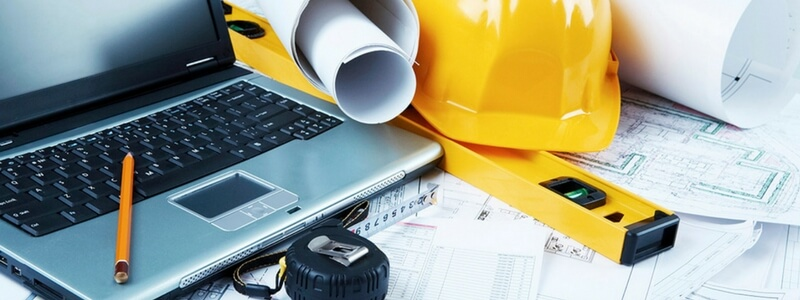 Laptop, yellow hard hat, level, blueprints on desk