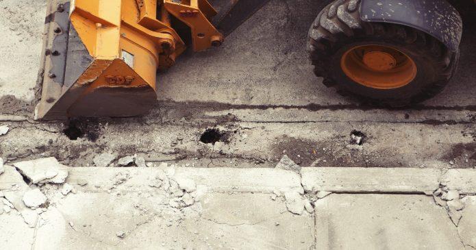 Big tractor repairing a broken road