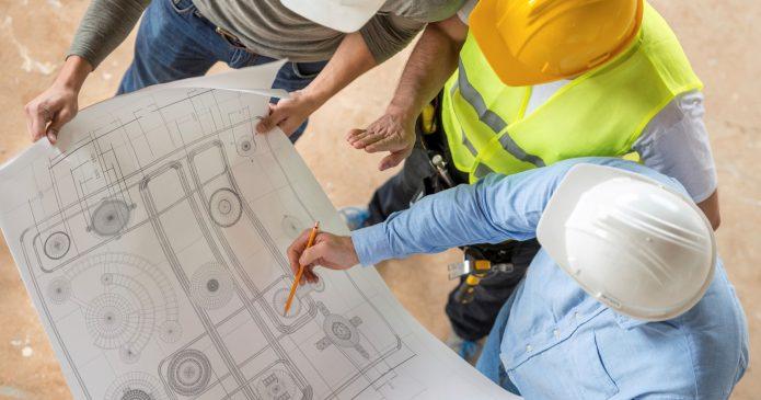 3 men reviewing construction drawing