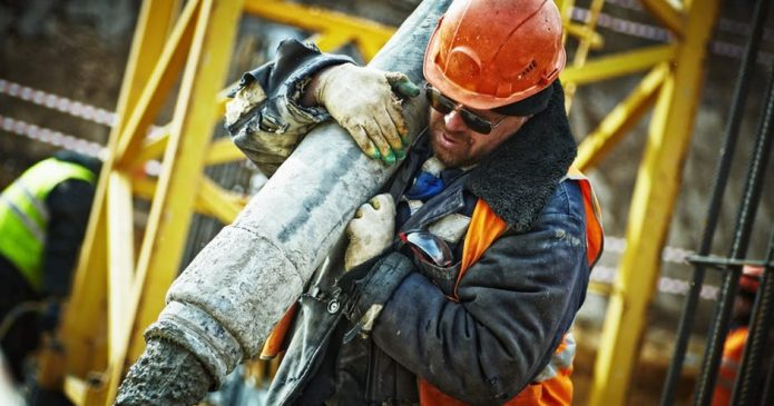Construction worker carrying a pipe